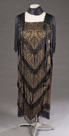 ~A 1920s beaded dress with contemporary head dress. Bead embroider on black silk and sleeved. Repeating diamond pattern outlined in black beads on top of chevron pattern with beaded ends~
