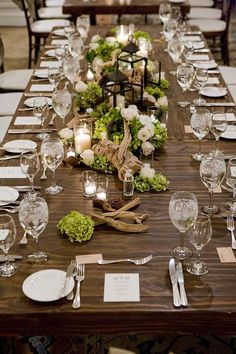 This is the closest I've found to the tablescape I have imagined. Instead of driftwood, place slabs of wood throughout the table, also creating elevation. The flowers would still be randomly placed, and a couple lanterns as well as a bajillion candles everywhere. BINGO.