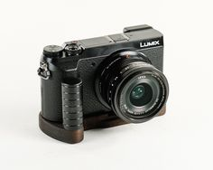 """J.B. Camera Designs Pro Wood Grip for Panasonic GX85 GX80 - Handmade in the USA. J.B. Pro Wood Grip adds improved ergonomics, increased protection, and unique look to your Pro Digital Camera. Due to demand of our handcrafted product - please pre-order and I will ship by the """"Release Date"""" listed here. My Pro Wood Grip is made of strong Peruvian Walnut and the vertical post is custom machined out of solid aluminum and then anodized to give a unique texture & professional look. Each J.B…"""