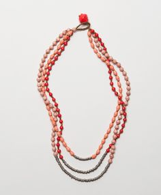 Romantic loops of upcycled paper beads make this piece an eye-catching addition to your favorite date-night ensemble.