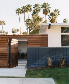 A lush green lawn and shrubs soften the steel and concrete, while tall palm trees beckon in the distance on the grounds of this chic and modern home.