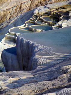 Pamukkale es una formación por sedimentación de calcio, que a lo largo de cientos de años modeló una cascada blanca en forma de terrazas en la región del Egeo en Turquía. Los piletones, son además un parque de aguas termales natural.