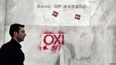 """A pedestrian walks past the bank of Greece with """"NO"""" signs referring to the upcoming referendum in Athens, 2 July, 2015."""