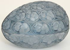 A Rene Lalique egg-shaped covered box Pousssins, circa 1929.  The frosted and molded baby chickens individually surrounded by a molded egg, raised block letter signature R. Lalique.