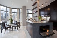 Nice modern kitchen and dining area with the waterfall countertop - cool touch with the contemporary fireplace