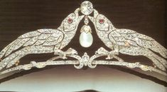 A later belle epoque bandeau, possibly with a missing aigrette feather; designed as two diamond birds, with ruby eyes folding a diamond and pear-shaped pearl.