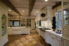 This kitchen's white painted cabinetry, built-in storage nook, and decorative corbels, give the room an English countryside feel. Roughly hewn wood panels and beams grace the ceiling, and a knotty wood floor adds to the Old World style of this kitchen.    Designed By: Drury Design  Glen Ellyn, IL