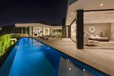 Floor-to-ceiling windows provide an excellent view of the 65-foot infinity pool that borders this stunning contemporary home. A terrace outside of the bedroom serves as a great spot to relax outdoors and also creates the perfect space for warm-weather entertaining.