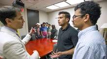 Niagara College students Anish Goyal, centre, and Rajendra Prasad Apppidy, right, speak with lawyer Ravi Jain on Thursday. (J.P. MOCZULSKI/J.P. MOCZULSKI)