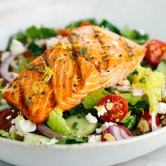 Light, fresh and healthy grilled salmon Greek salad recipe. Crisp vegetables are tossed in a tangy lemon basil dressing and topped with flaky salmon.