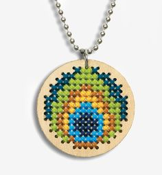 Dimensions Peacock Pendant - Cross Stitch Kit. Create a stylish fashion accessory with this counted cross stitch wood pendant. The Peacock Pendant by Dimensions