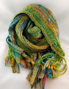 Handwoven scarf using handspun corespun textured yarn, handspun BFL, and sari ribbon. The weft is handspun silk. A heavier scarf but warm and