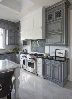 White and gray kitchen features gray wash cabinets paired with black granite cou. - White and gray kitchen features gray wash cabinets paired with black granite countertops and a gray - Dark Grey Kitchen Cabinets, Gray And White Kitchen, Kitchen Cabinets Decor, Farmhouse Kitchen Cabinets, Kitchen Cabinet Design, Black Kitchens, Kitchen Interior, Home Kitchens, Kitchen Backsplash