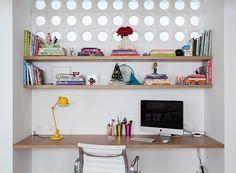 O arquiteto Felipe Hass adaptou um pequeno escritório na sala de estar deste apartamento e a solução para abrigar todos os materiais necessários foi apostar nas prateleiras. Elas poupam espaço e deixam o visual clean. (Foto: Fran Parente/Editora Globo)