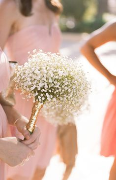 Baby's breath bridesmaid bouquet wrapped in gold.  @weddingchicks