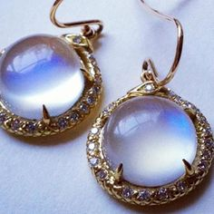 Bewitching TEMPTRESS earrings from Nora Kogan. Blue moonstone cabochons ringed in 18K gold and diamond pave.