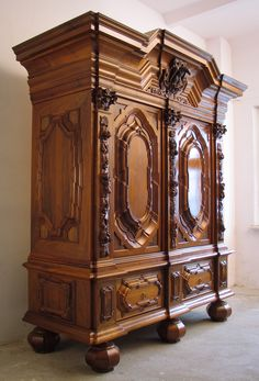 Richly decorated two-door wardrobe. Two drawers at the bottom. The door panels are framed with pilasters topped with carved capitals. A top of a repeatedly cut and broken moulding, decorated with carved coat of arms with a motif of an eagle against a background of acanthus leaves. Dimensions: H 2.4 m; W 1.8 m; D 0.7 m. Material - European walnut on a pine frame. need more details? write us: info@meble.gda.pl
