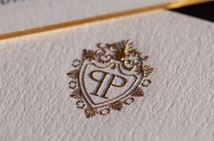 Black-tie invitation with gilded edge and a detailed crest in gold thermography. Lavish yet understated elegance.   Design and printing by http://www.printicon.com