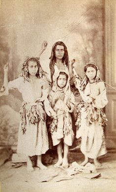 This photograph was executed at Bucharest, in 1869 (Photographed by Carol Szathmari, Bucharest.) At the arrival of spring, it is the custom in Roumania, Servia, and Bulgaria for a group of Gypsy children, quite alone, or under the guidance of a woman or an older girl, themselves only halfclad or actually naked, and having their heads and loins wreathed about with green branches of wild plants, to go from one house to another, before each of which they dance and sing a certain song.