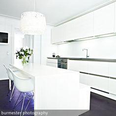 """Der dunkel gefärbte """"Pandomo"""" Fußboden von Naturo bildet einen kräftigen Farbakzent zu den weißen Küchenmöbeln. …"""