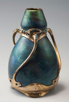 Art Nouveau vase with metal mounting, circa 1900. Pottery by Zsolnay. Mounting designed by Friedrich Adler and manufactured by Walter Scherf. Blueish-golden eosin glaze, gilt pewter mounting with turquoise precious stones. Marked: OSIRIS 642, 15, 35. Measures H. 15.1 cm. | SOLD 2,200 EUR, 2011