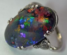 Splashing colors, ever changing, define this wonderful black opal ring set in 18K white gold with diamonds. The stone weighs 6.25 cts. Glorious in daylight and magical by candlelight. (alternate view)