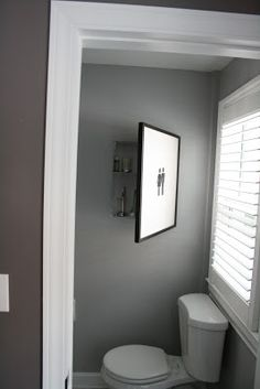 Art that opens up to hidden bathroom storage. CharmingDoodle