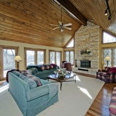 Stone fireplace, exposed beams, wood ceiling, and lots of natural light. #FamilyRooms #Design