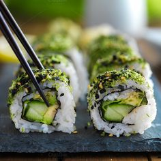 picking up a piece of green themed kale veggie sushi with cucumber and avocado.