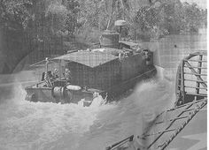 An assault support patrol boat (ASPB) of Task Force 117 slowly moves up the outboard quarter of an armored troops carrier (ACT) as it sweeps for Viet Cong command detonated mines. Despite the determination of the enemy the ruggedly built vessels, mostly converted landing craft were tough to knock out and could take a lot of punishment.