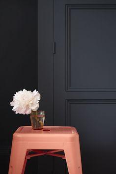 peach metal stool against black wall, pantone blooming dahlia, coral peach, salmon pink