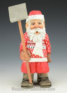 """""""Santa is ready for a little work with the snow shovel. He wears a Christmas sweater and white scarf. A hand crafted Santa Claus figure, carved from solid wood. Designed, carved by hand, painted, finished and signed by Russell Scott."""""""