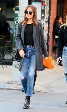 Fifty Shades actress Dakota Johnson showing that you can't go wrong in a classic pair of blue stonewash jeans teamed with a simple black knit and grey blazer. The Gucci boots up the ante