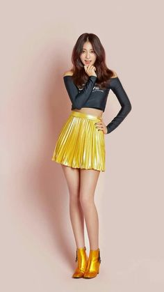 Asian girl in shiny yellow pleated miniskirt and metallic gold ankle boots