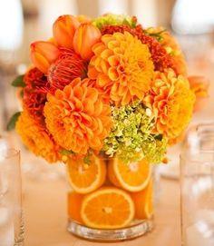 Centro de mesa con dalias y muchos otros tipos de flores: el toque de distinción está en las naranjas dentro del florero.   www.florama.mx