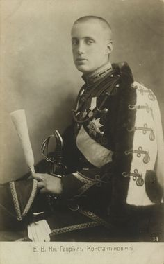 Postcard do Príncipe Gabriel Constantinovich (Gavriil Konstantinovich) em 1910. Ele está sentado virado para a esquerda com a cabeça voltada para a câmera. Ele está vestindo uniforme militar com um casaco de pele forrado em seus ombros. Ele está segurando uma espada e um chapéu com uma pluma. Há uma legenda em russo abaixo.