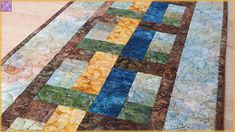 Quilted table runner is made with these beautiful Batiks in golden yellow, olive green, blue and brown. Will make a beautiful addition to your dining/kitchen table, sideboard, coffee table, kitchen island, dresser or credenza. Double folded binding has been machine stitched to the front