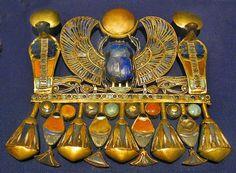 """Pectoral de Toutânkhamon avec pierres semi-précieuses, représentant l'un des noms titulaires du pharaon, """"le nom de Nesout-bity"""" (nom de couronnement), ainsi que des hiéroglyphes de paniers, des fleurs de lotus, le scarabée ailé poussant le disque solaire, entouré de serpents, l'ânkh & l'Oudjat, l'œil d'Horus - Trésor du tombeau de Toutânkhamon."""
