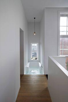 Badkamer maatwerk in Solid Surface materiaal HI-MACS. mooi contrast met de industriële warm gewalste blauw stalen schuifdeuren en de eiken vloer. Ontwerp: Witteveen Architecten