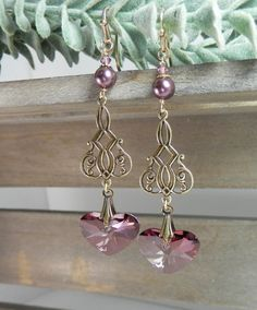 These earrings showcase beautiful modern shaped hearts of Swarovski lilac shadow crystal. They hang from gold finished, lead and nickle free, brass filigree links below round freshwater pearls. The earrings are finished with high quality, sturdy gold filled ear wires.  Earring length is 2 3/4 inches. All items are giftboxed and ready for giving.  What is gold filled? Gold Filled products have approximately 100 times more gold than gold plated products. Gold filled looks and wears as well...