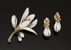 A late 19th century enamel and diamond bangle brooch and earclips. The hinged bangle designed as an interlocking stem set with rose-cut diamonds to white enamelled triple bud detail one bud detached; the earclips of matching bud design; the brooch designed as an opening flowerhead with white enamel petals and buds, old brilliant-cut diamond filaments and rose-cut diamond stem