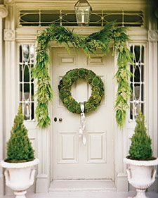 Fantastic containers in white grace this greenery adorned entry