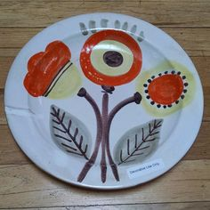This handmade, hand painted decorative platter, depicting a handful of mid-century flowers, would look great hanging on the wall of a mid-century modern home!