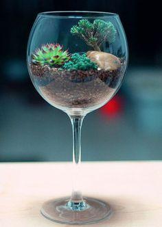 Numa taça de vinho, terra de diferentes cores são completadas pela vegetação verde, com toque especial da pedra em marrom.