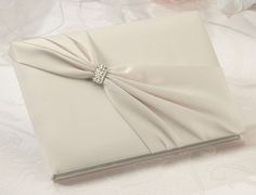 "- This elegant ivory satin guest book is decorated on the front with an ivory satin sash and rhinestone ornament.  The book measures 8.5"" x 6"" and holds 55 pages for a total of 990 signatures.  A matching pen set is sold separately."