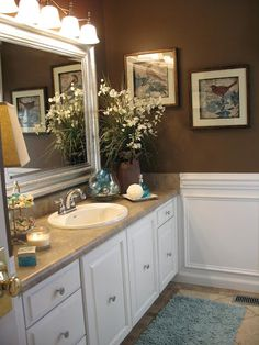 DIY..Small Budget Cottage Bath Makeover/ white wainscotting; brown color; frame around mirror; repaint cabinets; new floor; move heating vent; enlarge window