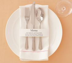 Place setting with menu printed on white paper ring napkin holder