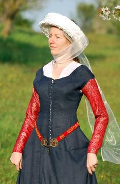 "The clothing consists of the blue linen laced dress. Silk brocade separate sleeves are pined to the short dress´s sleeves. A scarf elongated to the point at the back is inserted to the neck opening. The headwear consists of transparent veil and a fringed band. Below the waistline is a red belt with hand-made gold embroidery ""De gustibus et coloribus non est disputandum""."