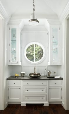 Country butler's pantry features see through cabinets flanking porthole window over white inset cabinets paired with gray countertops atop vessel bowl sink.