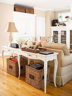 A table behind your couch adds extra space for your stuff. Add baskets underneath for even more storage.